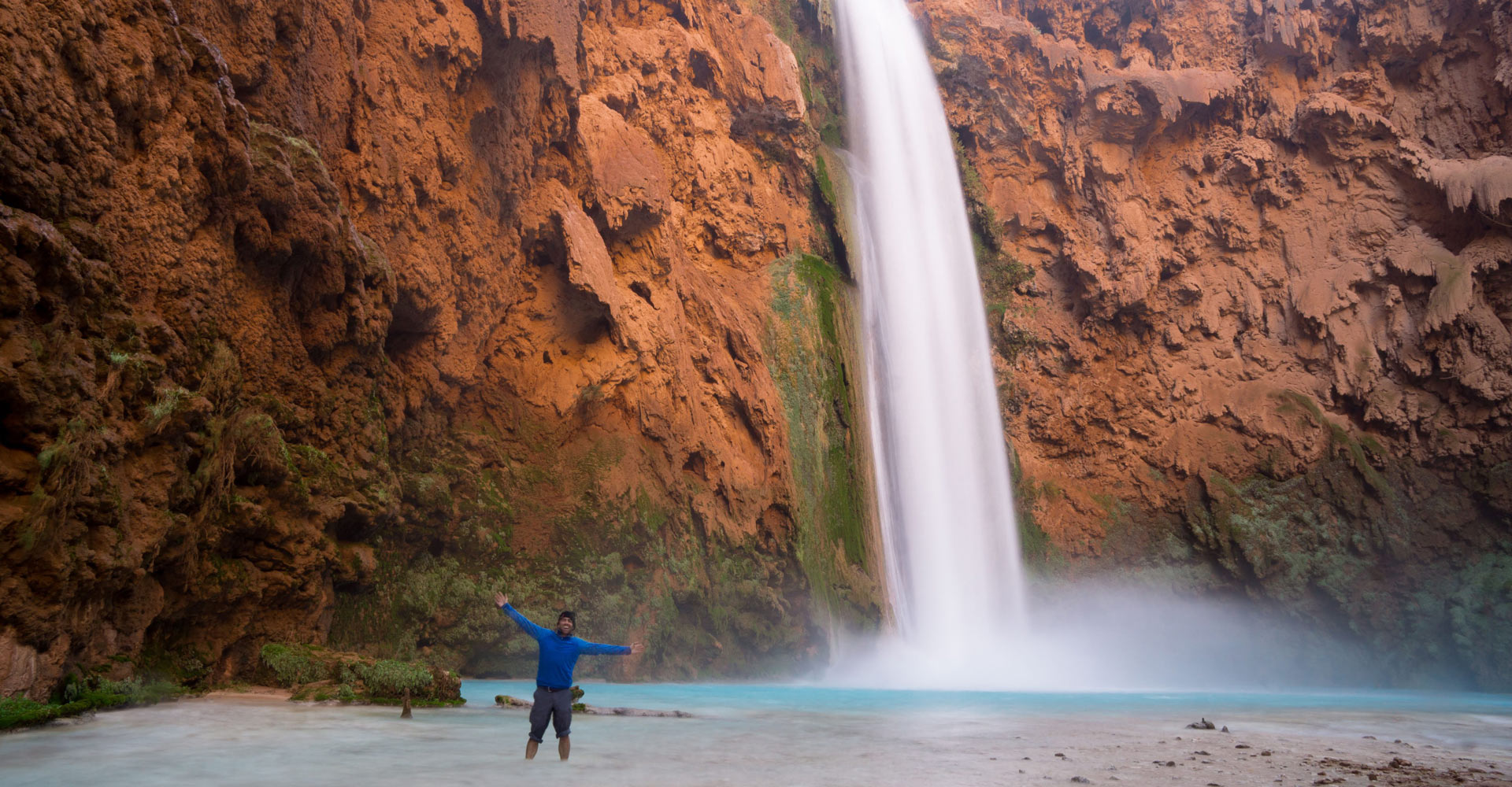 Nick from Mountain Mojo Group standing in front of waterfall at Havasupai